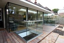 Project: Courthope Road / A rear glazed extension using IQ's minimally framed sliding glass doors on three sides and a frameless glass rooflight above. To the external decking glass balustrades allow light through lightwells into the basement courtyard below