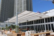 Beach Club Retractable Canopy / The Beachwalk, a new luxury condominium development at Hallandale Beach, near Miami, needed a protective cover for a terrace that overlooks the Atlantic Ocean. The client requested a 25-ft-by-70-ft-wide Tenara Fabirc canopy for a second floor terrace used by the bar &  restaurant at the condo's private beach club.