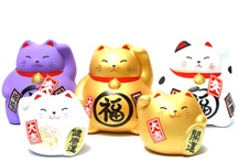 """Maneki Neko/Lucky Cat / De betekenis van de Maneki Neko of Lucky Cat is """"wenkende kat"""". Geef je vriendin, moeder of zus een Maneki Neko/ gelukskat kado, als blijk van genegenheid. De kleur van het katje heeft een positieve betekenis, zoals financieel geluk (goud), geluk in de liefde/huwelijk (roze of rood), goede gezondheid (groen), reinheid (wit. De katjes zijn gemaakt van uitstekende kwaliteit porselein en zijn afkomstig uit Japan.  Kadotip: verjaardag, """"geslaagd"""", samenwonen, bruiloft."""