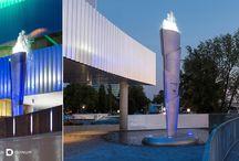 Fina Fontain / A FINA szökőkutat az idei világbajnokság fő helyszínén, a budapesti Duna Aréna folyóra néző oldalánál helyezték el. Tervezési alapelvünk volt, hogy dinamikussá tegyük az első körben statikusnak elképzelt obeliszk formát. Az alaptestet felszabdaltuk és a pajzsszerű részelemek balra-jobbra eltolásával izgalmasan vibráló hatás keletkezett, mely nagyon jól illeszkedik az épület homlokzatának struktúrájához.