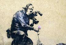 Banksy / Banksy is het pseudoniem van een wereldbekende Britse kunstenaar. Hoewel er weinig zekerheid is over de ware identiteit van Banksy en de meeste bronnen aangeven dat zijn echte naam Robert of Robin Banks is, heet hij waarschijnlijk Robin Gunningham. Hij zou in 1973 geboren zijn in Bristol. Zijn kunstwerken zijn vaak politiek en humoristisch van aard. In zijn straatkunst combineert hij graffiti met een hem kenmerkende sjabloontechniek.