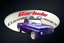 1965 Custom Step-Side Pick Up / This 1965 Chevy Custom Step-Side Pick Up built by Carlisle Customs and Classics features a custom molded hood, shaved door handles, custom integrated tail and marker lights, air-ride suspension, a custom two-toned leather interior, a hard wood and chrome covered bed, and glossy purple paint.