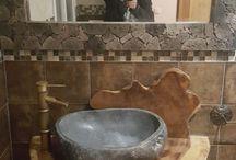 lavabo en madera de suar  y piedra de río.  con espejo de piedra volcánica.
