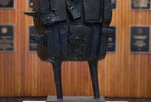 """Bernard Meadows / Bernard Meadows trained under Henry Moore in the art of direct carving.  However, after a trip to Italy where he saw sculptures of emperors and generals, he shifted from depicting mostly abstract animal motifs as symbols of the human condition to a series of twenty sculptures of human figures clad in armor as if needing constant defense against physical and psychological threats. """"Augustus"""" is located in the JON lobby at the University of Texas at Austin. GPS: 30.288587,-97.731345"""