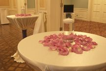 bistro tables with lavender rose petals and a tall cylinder vase with a floating candle.