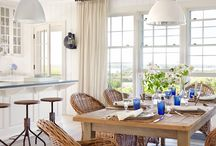 Dining on the Coast / A coastal dining room is as casual and relaxed as a summer night spent laying on the beach. Details like chic shell chandeliers, slipcover dining chairs, and weathered wood tables populate this look in a stark white palette with pops of blue and turquoise inspired by the blissful contrast of sand and sea.