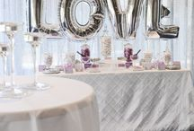Lilac and Silver Candy Bar / Adorned with a silver sequin backdrop and silver letter Geronimo balloons for this beautiful engagement party. White pintuck tablecloth set the base for this sophisticated and fun candy bar, with custom designed chocolate wraps and candy bar accents, with geometric elements to compliment the selection of white, silver and lilac candy. All brought together with mirrors, sequin elevations and carefully curated apothecary jars. Youtube: https://www.youtube.com/watch?v=OFlCoB3tFVA&feature=youtu.be
