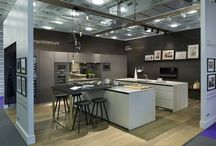 100% Design 2015 / bulthaup by Kitchen Architecture 100% Design at Olympia 2015: Islands in Kitchen Architecture's bulthaup b3 furniture in gravel laminate and a stainless steel work surface   Wall panels in Kitchen Architecture's bulthaup b3 black-brown structured oak and anthracite laminate with structured oak shelves