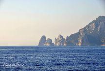 Capri / Capri è un'isola di origine carsica. Inizialmente era unita alla penisola Sorrentina, in seguito fu sommersa in parte dal mare e separata dalla terra ferma. Capri presenta una struttura morfologica complessa, con cime di media altezza e vasti altipiani interni, come Anacapri. La costa è frastagliata con numerose grotte e cale che si alternano a ripide scogliere. Fra le grotte la più famosa, è la grotta azzurra. Molto celebri sono i faraglioni.
