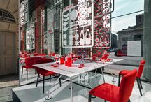 Tecno Lively Table / The installation designed for Tecno transforms the beautiful Piazza XXV Aprile into a urban living room. Four long red seats define the piazza in front of the Caselli. Continuous volumes for welcoming urban seats which slowly raise into exhibition spaces for the most iconic Tecno pieces.