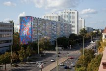 """LOA Berlin / Lichtenberg Open ART (LOA Berlin) ist eine Kunst- und Bildungsinitiative in und aus Berlin-Lichtenberg. Kern des Projektes ist eine wachsende Urban-Art-Galerie quer durch den Bezirk. Künstler gestalten Häuserfassaden als """"größte Leinwände der Welt"""". Das Ziel: Kunst in das Stadtbild zu integrieren und mit kreativem Blick neue Perspektiven auf Lichtenberg zu öffnen."""