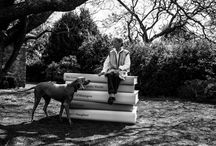 Nadine Gordimer - Behind the Scenes / Gordimer sits on top of a pile of her own works looking demure but strong. Shot in her Johannesburg garden beneath a jacaranda tree. Always believing the Word bigger than herself, here she is dwarfed by her work. The gigantic sized books are symbolic of her immense contribution to literature and South Africa. In recognition of this Gordimer was awarded the 1991 Nobel Prize in Literature.