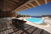 Angels Nest Villa Mykonos / The Angels Nest Villa is a 480 m2 stylish property, located in the Fanari area of Mykonos, the region with the highest elevation on the island offering to their privileged guests a stunning panoramic view of sunsets and the Aegean Sea, being the ideal setting for relaxing vacations and romantic getaways in the cosmopolitan and famous island of Cyclades in Greece.