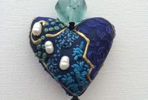 Hearts /  The pendants are handmade. The heart shape is made from silk fabric which is firmly filled, creating a small heart-shaped 'cushion'. The silk is embroidered with cotton and Japanese silk ribbon. The hearts are adorned with glass, ceramic and semi-precious beads, fresh water and cultured pearls and silver beads. The hearts are attached to strong cotton twine which is tied with a sliding knot so the pendant can be worn long or short.