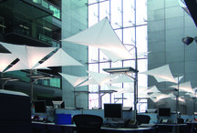 PWC HQ, Dublin / Sleek triangular panels of SEFAR® Architecture's interior polyvinylidene (PVDF) fabric gracefully float above a large work area atrium at the new PricewaterhouseCoopers head office in Dublin, Ireland. The office was built to house 2,000 employees, and is located at the high-profile Spencer Dock complex in Dublin. Comprising over 20 hectares of land along Dublin's Liffey Quays, Spencer Dock is the most ambitious urban regeneration project ever undertaken in Ireland.