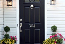 Front Exterior / Black exterior lights,  satin nickel hardware on a navy door that embellish our stone home.