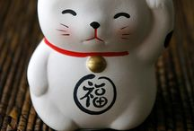 Maneki-Neko - lucky cat / Traditional Japanese cat with a raised paw.