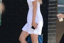 Gigi Hadid wears a white t-shirt dress, tennis shoes, sunglasses and a blue bag.