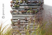 low budget vertical planting / Here greencube have designed a low cost, low maintenance, vertical planting idea, using offcuts of paving creating crevices to allow the sempervivums to grow.