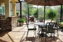 Flowers Edge Design / This outdoor design features a big patio partially screened in. It has a built in outdoor kitchen and a seating wall along the edge of the upper circular patio. Inside the screen there are beach rock accents and a perfect view of the lake.  This outdoor space is relaxing at anytime of day.