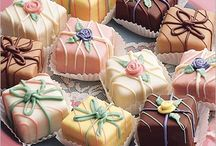 "Fondant Fancies, Petit Fours Etc / The petit four --- French for ""small oven"" --- is a small, sweet dessert that is no bigger than a cupcake liner and traditionally consumed after a meal. The classic petit four is a small square cake, lightly frosted, and often filled with chocolate or jam. Petits fours also frequently sport intricate designs that are applied in icing with small piping tips. Because of their small size, it can be a delicate process getting the piping as perfect as possible."