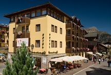 Hotel Touring Livigno / The hotel's central location makes it ideal for families, sports people and shopping fanatics alike. Large groups with also feel at home in the 48 guest rooms.        The rooms have been imaginatively designed. Each room is unique so you're sure to find just the right one for you.       À la carte restaurant Large rooms available for special events (weddings, birthdays, baptisms, gala events, etc.) for up to 180 people.  Live music nights.  A fixed price menu featuring local specialties.