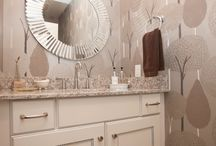 White and Gray Powder Room - Hingham, MA / This contemporary powder room design offers style and comfort to visitors and family.  The design maximizes the small space with a white vanity cabinet offering ample storage for a powder room.  The integrated countertop and backsplash complements the white cabinetry, patterned wallpaper, and round mirror.  Photos by Susan Hagstrom