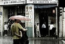 Umbrella and umbrellas / Il pleuvait fort sur la grand-route, ell' cheminait sans parapluie j'en avait un, volé, sans doute le matin même à un ami. Courant alors à sa rescousse, je lui propose un peu d'abri. En séchant l'eau de sa frimousse, d'un air très doux ell' m'a dit « oui ».