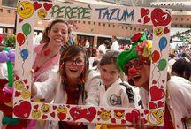 """Perepe'Tazum /  Gruppo pubblico Associazione di Volontariato Onlus di Ravenna, iscritta dal 2012 al registro provinciale delle organizzazioni di volontariato, con lo scopo di offrire sostegno e solidarietà attraverso il servizio dei volontari Clown che portano i loro sorrisi ovunque ci sia disagio e sofferenza. I nostri clown svolgono i loro servizi in modo assolutamente volontario e gratuito.  Andiamo principalmente all'ospedale Santa Maria delle Croci, convenzionato con la nostra Associazione, all'hospice Villa Adalgisa e saltuariamente prestiamo servizio durante feste organizzate da associazioni che si occupano di malattie gravi o disabilità e in appoggio a progetti sulla disabilità infantile. Non siamo clown professionisti ma lo facciamo con passione e serietà: puntiamo molto sulla formazione, che prevede uno stage iniziale di due giorni, stage di formazione specialistica e di aggiornamento e continui """"allenamenti formativi"""" due volte al mese. Per i nostri servizi è importante conoscere tecniche di mimo, improvvisazione, comunicazione verbale e non verbale e tutto ciò che fa parte del """"bagaglio"""" del clown, ma anche e soprattutto un approccio corretto con il paziente e con le strutture: andiamo con garbo e discrezione a donare un sorriso a chi soffre, con le nostre """"divise"""" (camici simili a quelli dei medici ma colorati e personalizzati da ognuno di noi, tesserino di riconoscimento e l'immancabile naso rosso) coloriamo l'ambiente ospedaliero ma la nostra allegria non vuole superare mai i confini del buonsenso e l'eventuale rifiuto: se un paziente non ci vuole - capita raramente - ci limitiamo a un saluto e a lasciare un palloncino colorato come segno della nostra vicinanza affettiva alla sua sofferenza.  NOTA BENE: I nostri volontari non prestano MAI servizio da soli, NON facciamo raccolta fondi porta a porta o nei supermercati, NON telefoniamo a casa, nessuno dei nostri soci è autorizzato a raccogliere singolarmente soldi o fondi per l'associazione."""