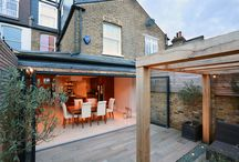 Pitched-to-hip Roof Kitchen Extension in Putney SW15 / The kitchen was extended into the side return and partially out towards the rear garden. Due to the limited space the garden was set to meet in at the same level with the kitchen floor allowing the two spaces to work as one when the large rear doors are opened up. The attention to detail on the finishes complements a bold wooden kitchen whilst the creative garden design provides a delightful view making this a striking and atmospheric entertaining space.