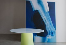 ADAM, tables / The base in rotomoulded polyethylene and is shaped by a triangle changing into circle. The tops are circular or elliptical, in compact grade laminate, clear crystal glass or back painted. Available in 2 different heights. A design of Busetti, Garuti, Redaelli, 2012.