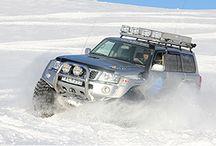 """Island Surprise / Denne safarien er kanskje en av de mest spennende i Norden!!!  islandsurprise-page  Gruppen blir hentet på flyplassen av Islandske Super Jeeper, som er kraftige ombygde biler. Hver bil har plass til 4 personer. Bilene har 44"""" – 46"""" hjul og mye spennende ekstra utstyr. Driverguidene som IceTour bruker er morsomme og kunnskapsrike gutter. De vil gi dere et adrenalinkick med sine monsterbiler som dere sent vil glemme."""