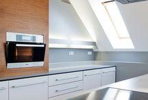 Anfreitung nach mass / Im typisch unbeschwerten Design der Plan 3 Küchen präsentiert sich der kompakte Küchenraum mit der zentralen Insel mit angenehmer Leichtigkeit. Die Skulptur, einzige Stütze des sonst frei schwebenden Arbeitsbereichs, dient gleichzeitig als Bar. Die Wandzeile mit ihrer indirekten Beleuchtung integriert sich perfekt, die aus Nussbaum gefertigte Box für Backofen und Kühlschrank zeugt von Liebe zum Detail und gibt der Küche einen ganz individuellen Charakter.