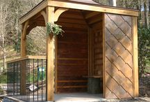 Copper Roofed Garden Room / Garden room created for RHS Rosemoor, featuring: -  Copper, concave roof -  Cedar shingles -  Oak posts -  Decorative oak struts -  Porthole lined with copper -  Iron ballustrade -  Oak handrail -  Assymetric stone paving -  Rustic oak bench -  Copper shingles -  Copper wall planter -  Copper roofed bird box