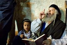 """dziadek żydowska uczy wnuka swoje modlitwy pod Ścianą Płaczu w Jerozolimie w Izraelu. / """"Tak Ja będę was pocieszał w Jeruzalemie."""" (Izajasz 66:13). Co za proroctwo! Ten werset mówi o pociesze w Kościele, o wszystkich członkach ciała Chrystusowego, którzy z miłością troszczą się o siebie nawzajem. Jest to obraz ludu Bożego, którzy przychodzą z ulgą dla zranień innych i wchodzą w ich cierpienia."""