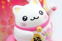 Maneki Neko / Le Maneki Neko (le chat qui invite) est une statue traditionnelle très répandue au Japon qui représente un chat assis, levant la patte au niveau de l'oreille. Il est célébré le 29 septembre au japon. https://mythologica.fr/japon/maneki.htm