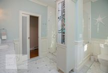 A Coastal Modern Design - Scituate, MA / This master bathroom design embodies the atmosphere of its beautiful seacoast location in the color scheme, design features, and use of coastal beach glass.  The Bianco Carrera marble floor and the shower are both complemented by glassblend mosaic details and crushed glass accents. This color scheme carries through in the green tint wall color.  The large double vanity includes plenty of closed storage and an open shelf for display.  Photos by Susan Hagstrom