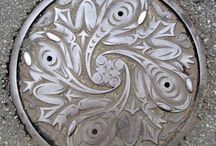 Manhole Covers. Street Grates.  / Always have loved the artistry of the humble manhole covers. Some more deliberately artful than others. Some completely, elegantly utilitarian. Some whimsical. Art right at your feet. Wonderful design, textures, patterns. Great for rubbings, collages.