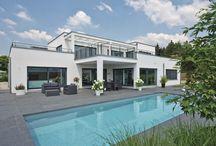 """Luxusvilla im Bauhaus-Stil / Architektonisch verbindet das individuell geplante Haus modernen Bauhausstil mit den Vorteilen des Wohnkonzeptes """"ebenLeben"""". Die Linien sind klar, schlicht und doch stilvoll. Besonders edel wirkt der Kontrast zwischen der weiß verputzten Außenfassade und den anthrazitfarbenen Holz-Alu-Fenstern."""