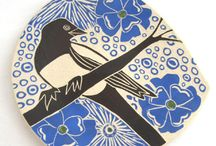 "Julia Janeway /  Each piece is hand carved from original patterns and drawings of my own. As I carve, I often wonder where the work will end up-- In a house in the Warsaw Woods? On some table in Italy? I wonder what story my work will tell someone else-- ""Take heart because there are goldfinch in the world!"" or ""You haven't realized it, but I know you love bears and I have always loved you"" or ""The time has come in our marriage for us to start raising chickens."" -Julia Janeway"