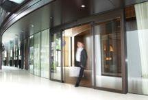 Automatische Prisma schuifdeur / Deze toegangsoplossing heeft een even originele als bijzondere uitstraling. De plaatsingshoek van de deur kan variëren van 90° tot 180° en zowel naar binnen als naar buiten worden gelegd. Met stompe hoeken wordt deze deuruitvoering in grote gradenhoek ook vaak geïnstalleerd in plaats van gebogen schuifdeuren.