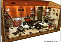 DIORAMA OFICINA MOTO KTM 990 - Personalizado - ANTONIO ALBERTO SOALHEIRO / 46L x 26P x 31H Em mdf encerado com óleo general iron fittings - tabacco, iluminação com leds, interruptor externo e fonte 110/220v. Escala 1/12, peças novas de plastimodelismo e recicladas de aparelhos eletrônicos, tv, som, relógios, bijuterias, madeira balsa, biscuit, com caixa de ferramentas para mensagem pessoal. Criação e impressão digital para quadros, papel de parede, livros, jornal, rótulos e piso, fazem parte da elaboração interna. Vidro superior articulado e frontal removível.