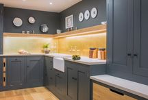 Modern Industrial Kitchen / The L-shaped design makes it easy to flow from one end of the kitchen to the other seamlessly. We wanted the brushed brass splashback to be the main feature in this kitchen. The cabinetry and walls are painted in Farrow & Ball Down Pipe. We decided wall units would take away too much light from the space so we went for an oak floating shelf  and half larder cabinet to utilise the space.