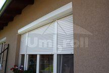 Redőnyök / A redőnyök tradicionális árnyékolók, melyek kiválóan alkalmasak régi és modern családi házak, társasházak, üzemépületek vagy irodák árnyékolására és védelmére. A redőnyök tetszőleges helyzetének beállításával szabályozható az árnyékolt épületbe jutó fény mennyisége. Leengedett állapotban tökéletesen védenek az UV sugaraktól és a kíváncsiskodó szemektől.
