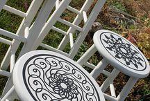Bancos de madera pintados de blanco con dibujos de arabescos en el asiento