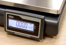 Wagi elektroniczne / Piny pokazujące, co można położyć na szalce wagi elektronicznej. I czym się różnią wagi platformowe od etykietujących. I że szalka może czasem lewitować, ale to nic złego. Na tablicy urządzenia znanych producentów, m.in. Dibal, Digi i Elzab.