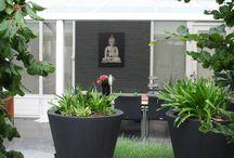 Kleine, moderne achtertuin / In deze kleine achtertuin is bewust gekozen voor grijs en wittinten en eenkleurig gevulde plantvakken voor een rustig effect. De beeldende kunst en de bijpassende tuinmeubelen en accessoires zorgen voor een geheel in deze uitnodigende buitenruimte.