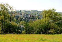 Pierre-Buffière / Pierre-Buffière, village étape, situé dans le Limousin sur la A 20, Sortie 40. Avec son bourg pittoresque aux bâtiments chargés d'histoire, ses tables de pique-nique à l'ombre d'un cèdre du Liban centenaire, Pierre-Buffière constitue une halte réparatrice à proximité immédiate de l'autoroute A20.