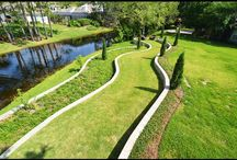 Italian Walkway Design / With the vertical growing trees and curved retaining walls traveling down the hill it's hard not to picture yourself in Italy. This design by 5 Star Outdoor Design is truly unique and offers a beautiful spot by the fire to relax and enjoy this one of a kind backyard. If you want a secluded spot all to your own all you have to do is follow the curved grassy path away from the house and you'll find a cozy spot with a couple of chairs to relax in the peace and quiet.