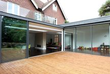 Project: Ashley Road / An L shaped contemporary glass extension in Walton on Thames showcasing IQ's slim sliding glass doors to all sides with a roof terrace above lined with frameless glass balustrades